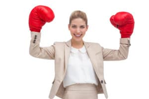 A smiling businesswoman holding boxing gloves on white background